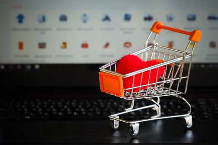 Red heart in a trolley on a laptop keyboard. Ideas about online shopping, online shopping is a form of electronic commerce that allows consumers to directly buy goods from a seller over the internet.