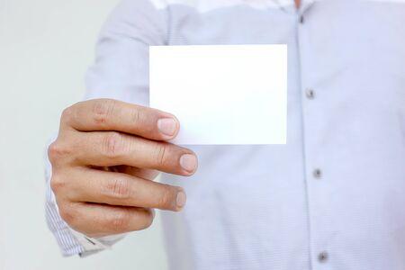 Mano humana mostrando tarjetas de visita - imagen de primer plano con fondo blanco.