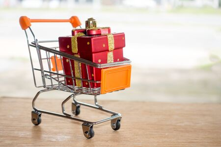 Red gift box in a shopping cart on wood table.concept online shopping.