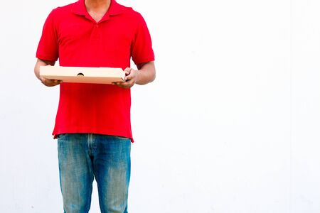 Delivery concept: Men in red shirts and hats are pizza dealers, carrying pizza boxes ready to deliver products to customers.