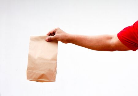 Male holds in hand brown clear empty blank craft paper bag for takeaway isolated on white background. Packaging template mock up. Delivery service concept. Copy space. Advertising area