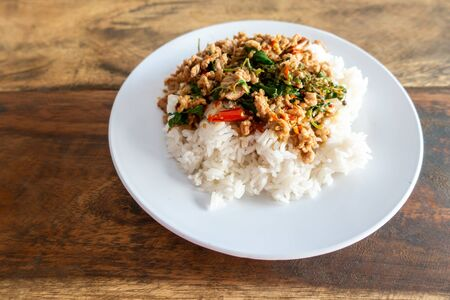 Rice topped with stir-fried pork and basil in a white dish. Stock fotó