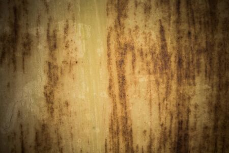 Old grungy cracked weathered wall paint peeling off rusted metal sheet. Textured background for posters and bloggers