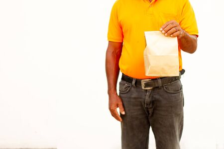 Holding various take-out food containers in holder and paper bag, close-up. Light grey background, place to insert your text. Delivery man.