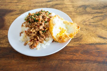 Rice topped with stir-fried pork and basil in  white dish on wooden table. , Text space. Stock fotó