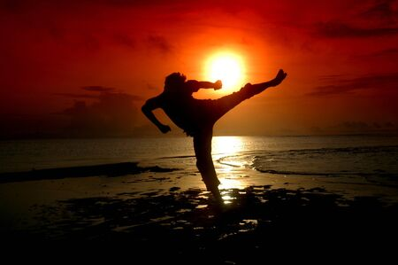 artes marciais: silhouette of a champion is being kicked by baground sunrise