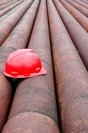 red helmet miner oil on an iron pipe in an oil mining area