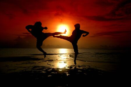 silhouette of two people who are fighting photographed before sunrise 写真素材