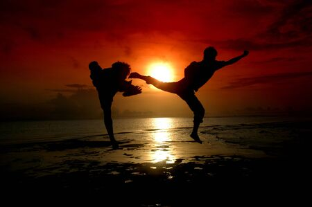 silhouette of two people who are fighting photographed before sunrise Stock Photo