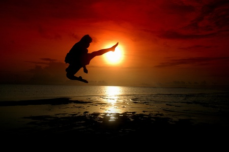silhouette of a fighter is kicking with sunrise background