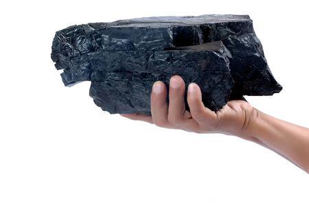 carbone: mano maschile in possesso di un grosso pezzo di carbone isolato su sfondo bianco