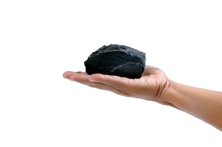 male hand holding a little lump of coal  isolated on white background Stok Fotoğraf