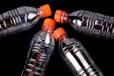 polycarbonate: four closed plastic bottles isolated on black  background