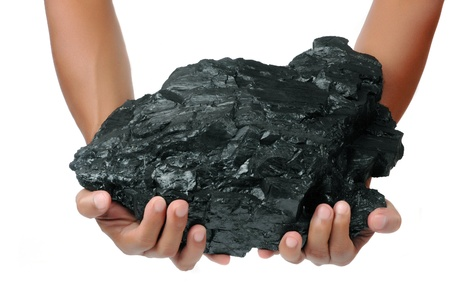 a big lump of coal is held with two hands isolated on white background 写真素材