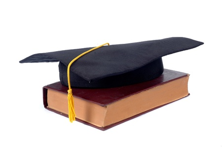 graduate cap and old book isolated on white background