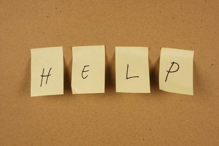 Ayuda escritura se escribe en una hoja de papel colocada en la caja de cartón marrón pared Foto de archivo - 10518027
