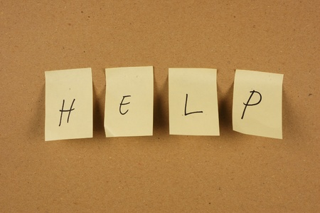 affixed: writing help is spelled in a sheet of paper affixed to the wall brown carton Stock Photo