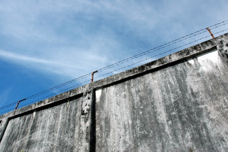 barbed wire fence: the prison walls with high walls and barbed iron wire Stock Photo