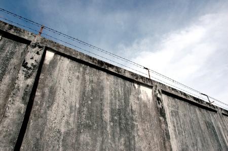 Los muros de la prisión con altos muros y alambre de púas de hierro Foto de archivo - 11817865
