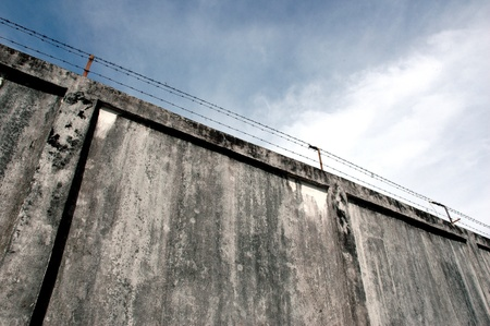 sky is the limit: the prison walls with high walls and barbed iron wire Stock Photo