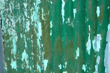 zinc wall with green paint color faded and cracked photo