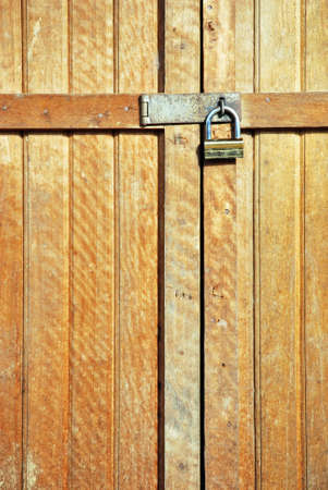 wooden door locked with a golden padlock photo