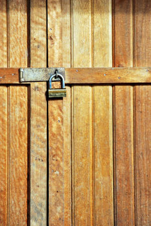 wooden door locked with a golden padlock Stock Photo - 12678452