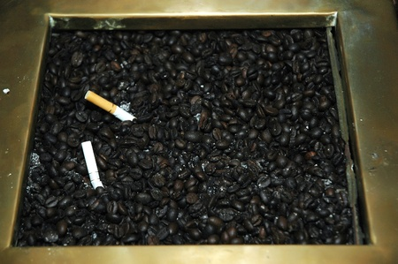 coffee beans as the ashtray to neutralize cigarette smoke photo