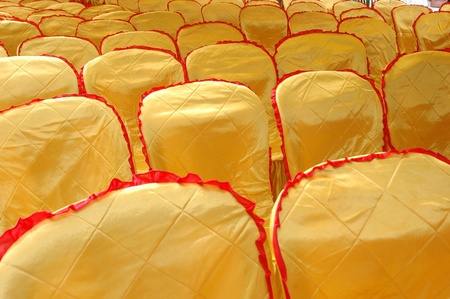 rows of seats with a golden yellow cover  photo