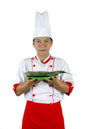 chef holding raw fish on a green plate isolated on white background Stock Photo - 13228173