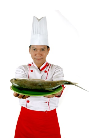 chef present raw fish on a green plate isolated on white background photo