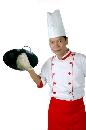 culinary skills: chef holding raw fish on a black frying pan isolated on white background