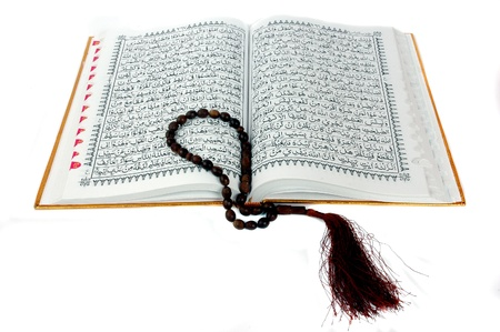 Al Quran and prayer beads isolated on white background