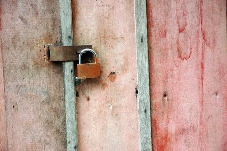 dull wooden doors locked padlock photo