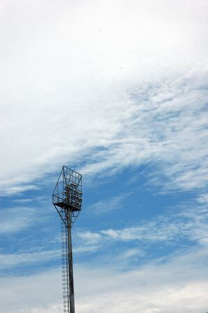 stadium light poles with white clouds and blue sky backgrounds photo