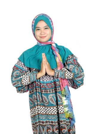 a beautiful muslim woman greetings with his palms pressed isolated on white background photo