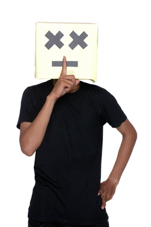 young boy make a sign to silent with his finger on his face from cardboard boxes against white background Stock Photo - 17726186