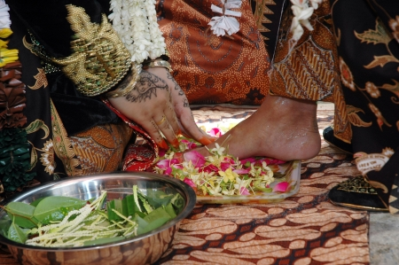 Indonesian traditional Javanese wedding ceremony, the bride wash the grooms feet