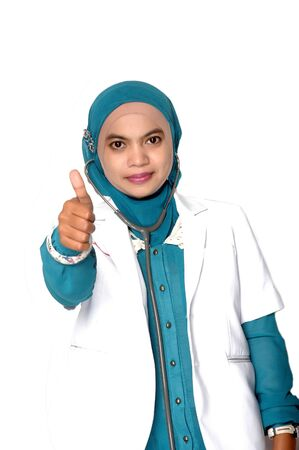 Asian young woman doctor thumbs up on white background photo