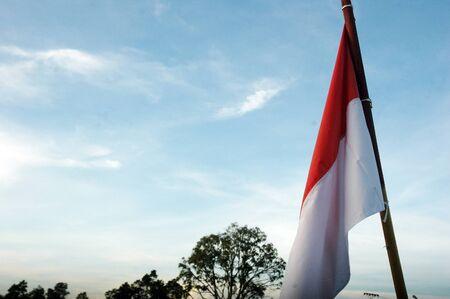 national flag indonesian flag: Indonesias flag against blue sky