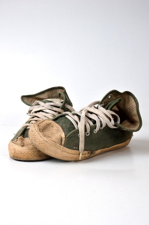 old used green sneakers on white background