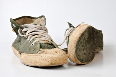 old used green sneakers on white background photo