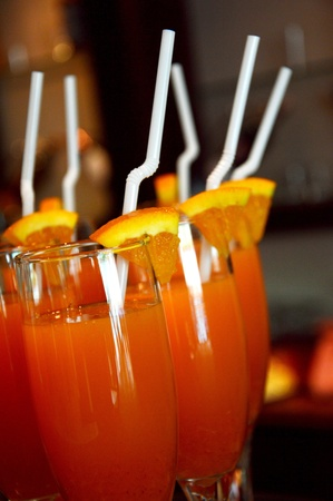 lots of orange juice with white straw and orange fruit slices photo
