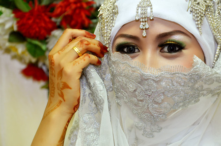 Beautiful Indonesian bride dressed in traditional white kebaya photo