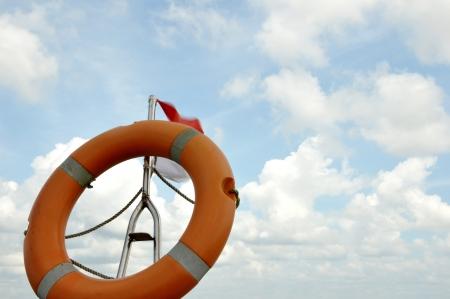 orange lifebuoy against blue sky photo