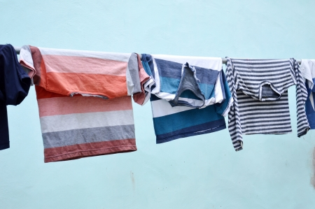 clothesline clothes with blue wall Imagens