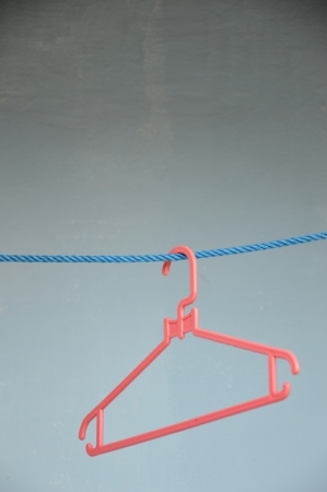 empty red hangers on blue line against blue wall photo