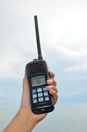 hand held: tenuto in mano walkie-talkie contro il cielo blu Archivio Fotografico
