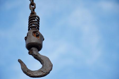 big old metal hook against blue sky photo