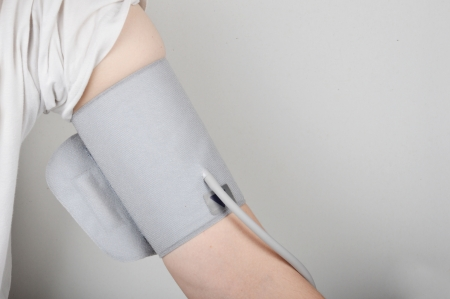blood pressure bulb: male arm wrapped with blood pressure gauge